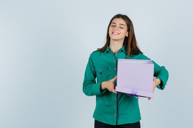 Junges mädchen, das geschenkbox hält, lächelt in grüner bluse, schwarze hose und schaut fröhlich, vorderansicht.