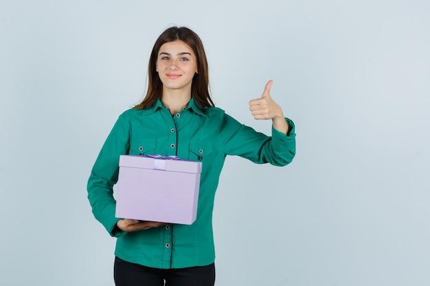 Junges mädchen, das geschenkbox hält, zeigt daumen oben in grüner bluse, schwarze hose und schaut fröhlich, vorderansicht.