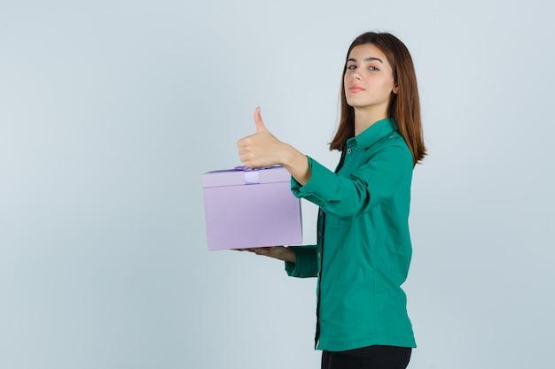 Junges mädchen, das geschenkbox hält, zeigt daumen oben in grüner bluse, schwarze hose und selbstbewusst aussehend, vorderansicht.