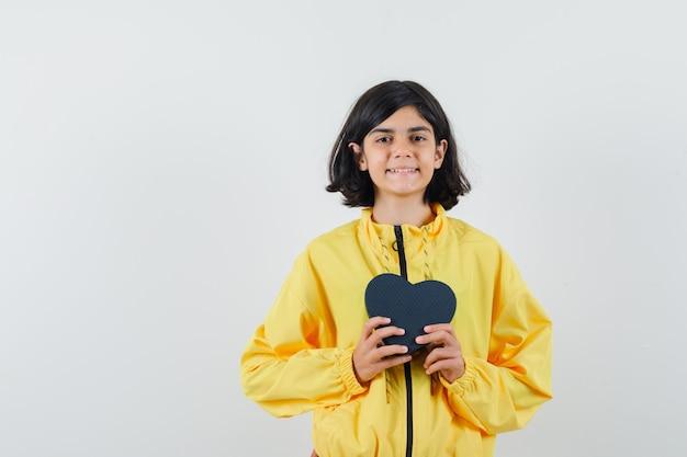 Junges mädchen, das geschenkbox mit beiden händen in der gelben bomberjacke hält und glücklich schaut