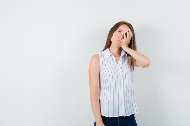 Junges mädchen, das gesicht auf erhabener handfläche im t-shirt, in den jeans lehnt und traurig schaut. vorderansicht.