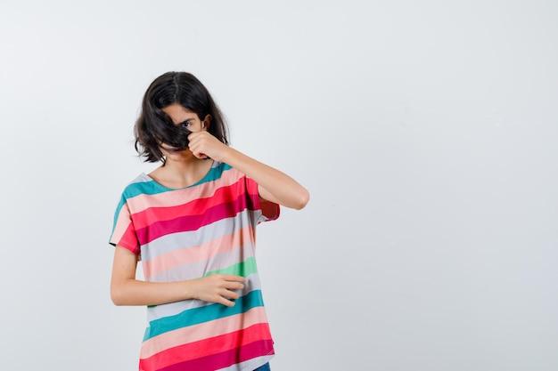 Junges mädchen, das gesicht mit haaren in bunt gestreiftem t-shirt bedeckt und süß aussieht, vorderansicht.