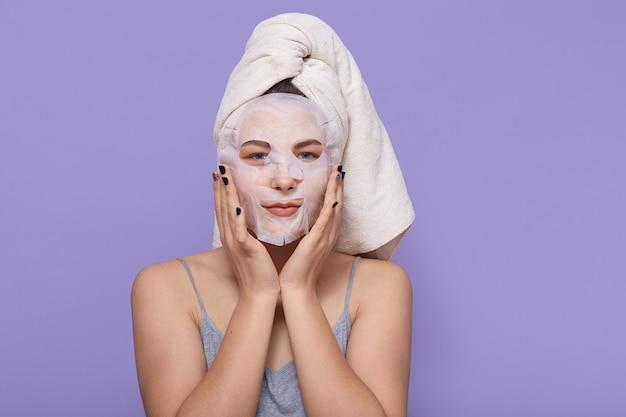 Junges mädchen, das gesichtsmaske anwendet, schönheitsbehandlungsverfahren tut, weißes handtuch auf kopf tragend