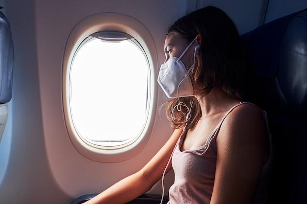 Junges mädchen, das gesichtsmaske beim reisen im flugzeug trägt