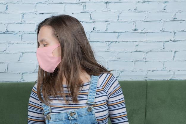 Junges mädchen, das gesichtsmaske trägt, um covid-virus zu verhindern