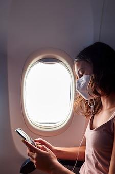 Junges mädchen, das gesichtsmaske unter verwendung des smartphones beim reisen im flugzeug trägt