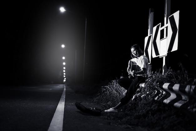 Junges mädchen, das gitarre auf straßenseite mit verkehrsschildhintergrund, reise des musikerkonzeptes sitzt und spielt