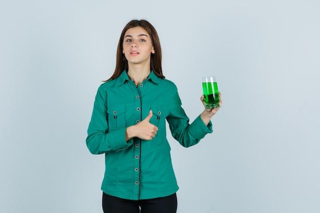 Junges mädchen, das glas der grünen flüssigkeit hält, daumen oben in der grünen bluse, in der schwarzen hose zeigt und ernst schaut. vorderansicht.
