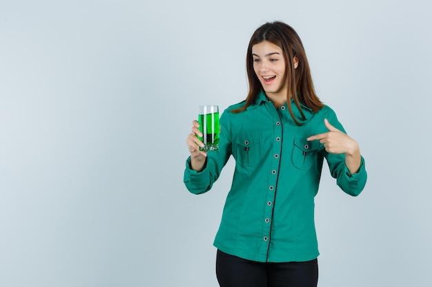 Junges mädchen, das glas der grünen flüssigkeit hält, mit zeigefinger in der grünen bluse, der schwarzen hose darauf zeigend zeigt und überrascht schaut. vorderansicht.