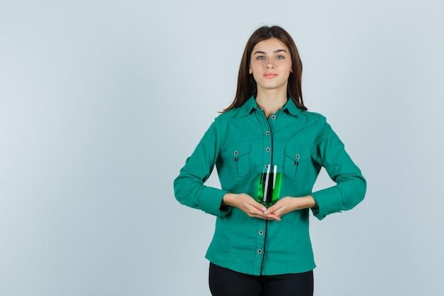 Junges mädchen, das glas der grünen flüssigkeit in beiden händen in der grünen bluse, in der schwarzen hose hält und fröhlich schaut, vorderansicht.