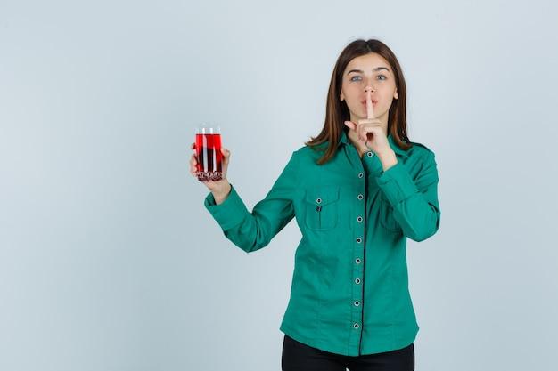 Junges mädchen, das glas der roten flüssigkeit hält, schweigegeste in der grünen bluse, in der schwarzen hose zeigt und niedlich schaut. vorderansicht.