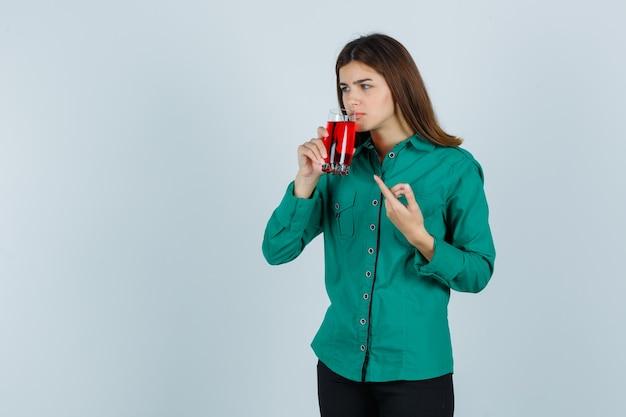 Junges mädchen, das glas der roten flüssigkeit trinkt, mit zeigefinger in grüner bluse, schwarzer hose darauf zeigt und konzentriert schaut. vorderansicht.