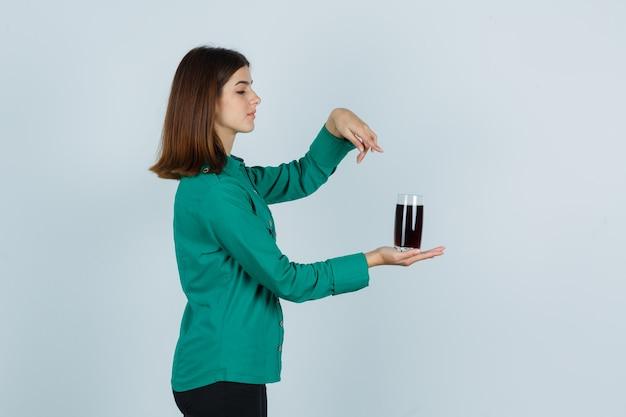 Junges mädchen, das glas der schwarzen flüssigkeit hält, es mit zeigefinger in grüner bluse, schwarzer hose zeigend zeigt und konzentriert schaut. vorderansicht.