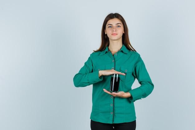 Junges mädchen, das glas der schwarzen flüssigkeit in beiden händen in der grünen bluse, in der schwarzen hose hält und fröhlich schaut, vorderansicht.
