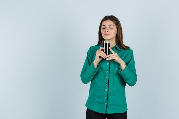 Junges mädchen, das glas der schwarzen flüssigkeit in beiden händen in der grünen bluse, in der schwarzen hose hält und glücklich schaut, vorderansicht.