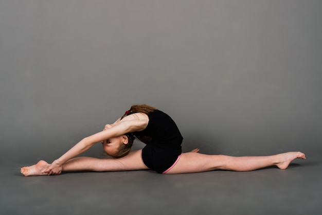 Junges mädchen, das gymnastik über grauem hintergrund, studio tut