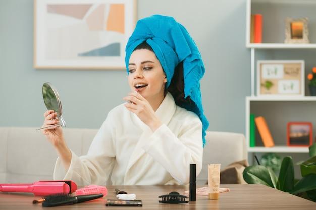 Junges mädchen, das haare in ein handtuch wickelt, das lippenstift hält und den spiegel betrachtet, der am tisch mit make-up-tools im wohnzimmer sitzt?