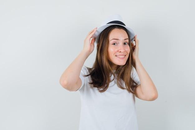 Junges mädchen, das hände auf ihrem hut im weißen t-shirt hält und hübsch aussieht. vorderansicht.