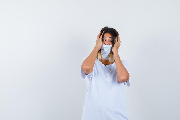 Junges mädchen, das hände auf schläfen im weißen t-shirt und in der maske setzt und besorgt, vorderansicht schaut.