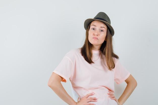 Junges mädchen, das hände auf taille im rosa t-shirt, hut hält und unzufrieden schaut, vorderansicht.