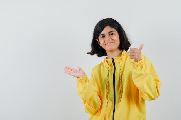 Junges mädchen, das hand linke seite streckt und daumen oben in gelber bomberjacke zeigt und glücklich schaut
