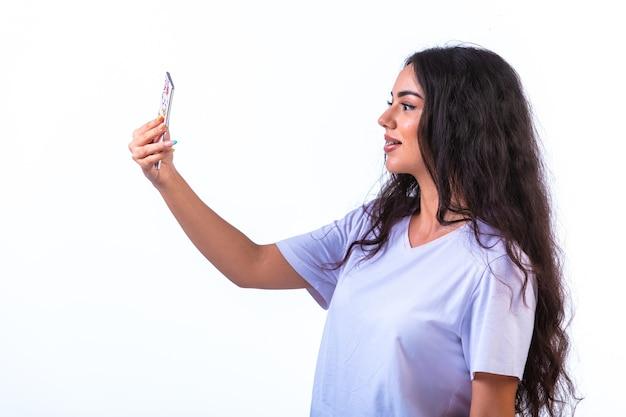 Junges mädchen, das ihr selfie auf dem handy auf weißer wand nimmt