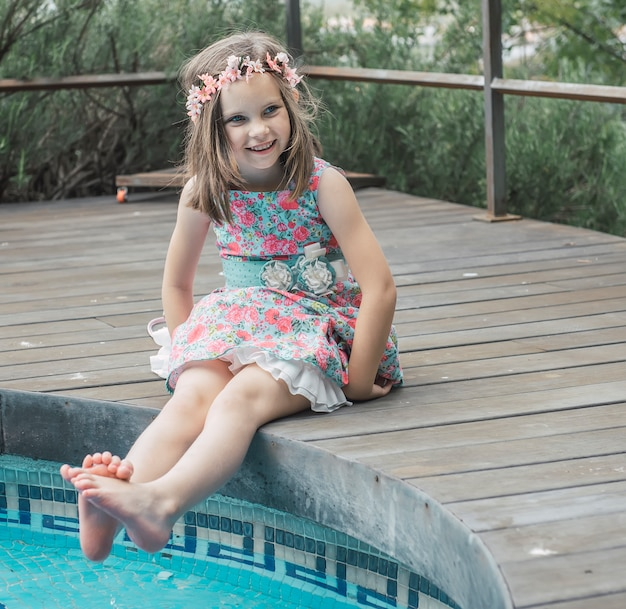 Junges mädchen, das ihre füße im wasser eines pools benetzt