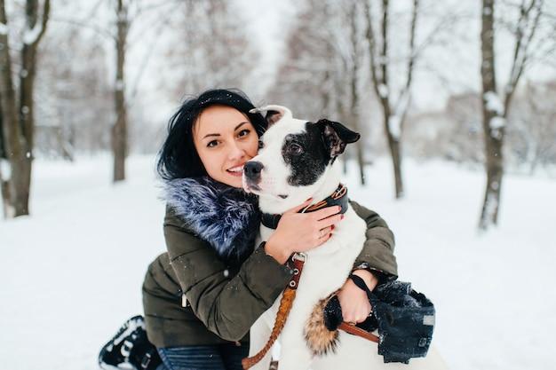 Junges mädchen, das ihren hund im winterpark umarmt.