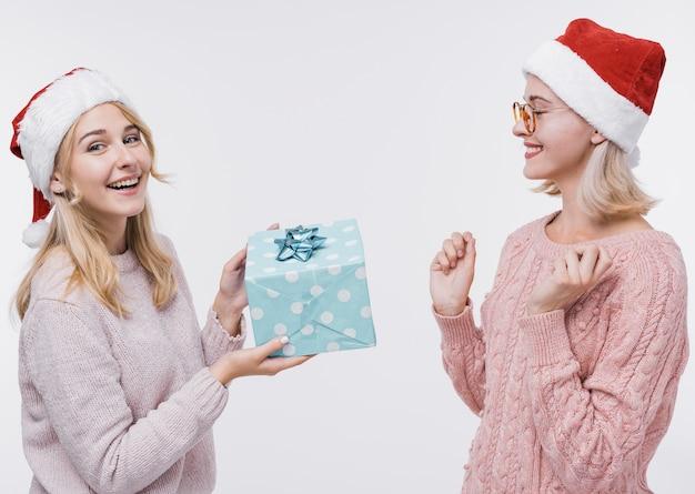 Junges mädchen, das ihrer freundin ein geschenk gibt