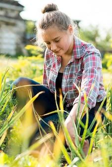 Junges mädchen, das im gras sitzt