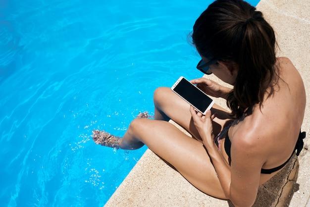 Junges mädchen, das im pool mit ihrem handy ein sonnenbad nimmt
