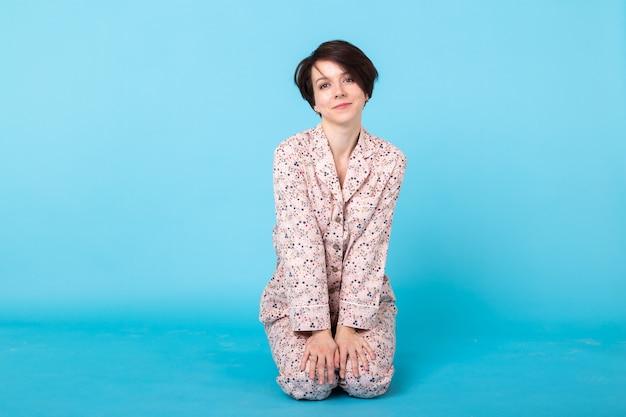 Junges mädchen, das im pyjama auf blauem hintergrund aufwirft. entspannen sie sich bei guter laune, lifestyle und nachtwäsche.