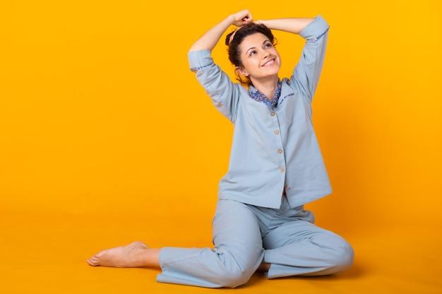 Junges mädchen, das im pyjama auf gelber wand aufwirft. entspannen sie sich bei guter laune, lifestyle und nachtwäsche.