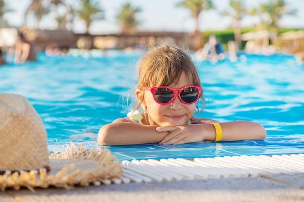 Junges mädchen, das im swimmingpool sich entspannt
