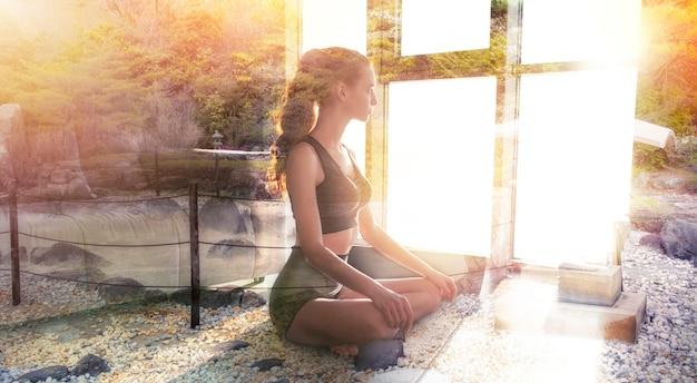 Junges mädchen, das in der yoga-position am haus mit zen-garten entspannt. doppelbelichtung