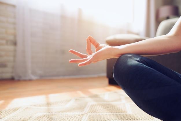 Junges mädchen, das in der yoga-position zu hause vor einem hellen fenster entspannt