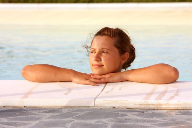 Junges mädchen, das in einem swimmingpool sich entspannt