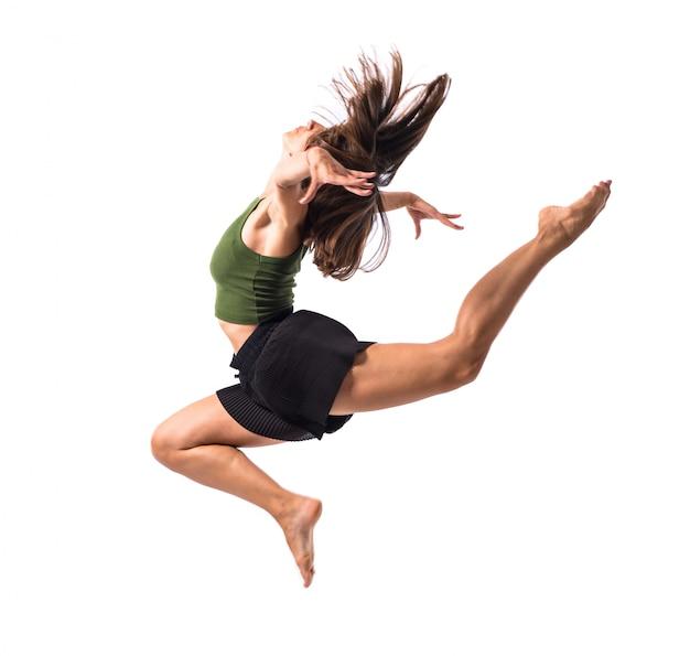 Junges mädchen, das in studio auf lokalisiertem hintergrund tanzt und springt