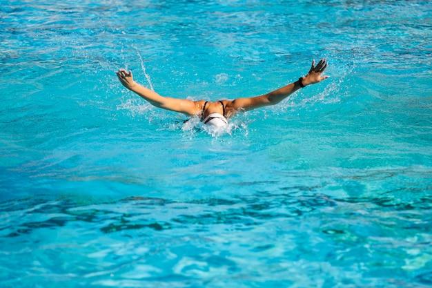 Junges mädchen, das innerhalb des schwimmbades aufwirft