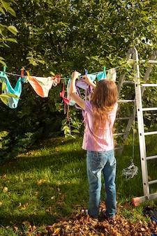 Junges mädchen, das kleidung an der wäscheleine im garten hängt