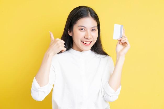 Junges mädchen, das kreditkarte mit glücklichem ausdruck auf goldenem hintergrund hält