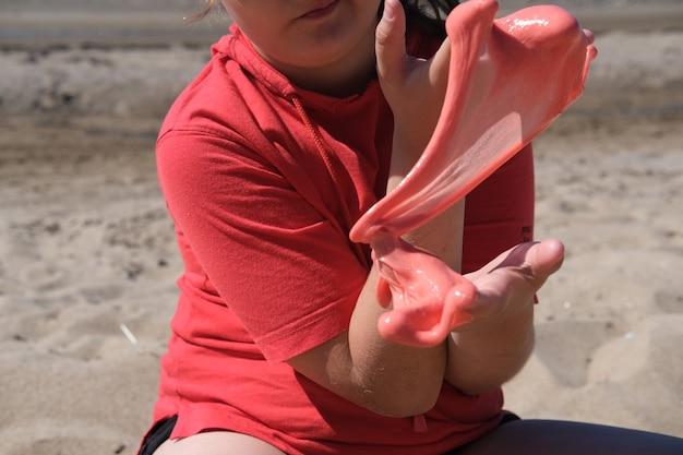 Junges mädchen, das leuchtend roten schleim in ihren händen hält bildung kreativität kindheit konzept selektiv