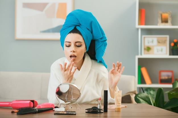 Junges mädchen, das lipgloss umwickelte haare in handtuch anwendet, das am tisch mit make-up-tools im wohnzimmer sitzt?