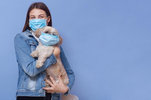 Junges mädchen, das medizinische maske mit ihrem haustier trägt