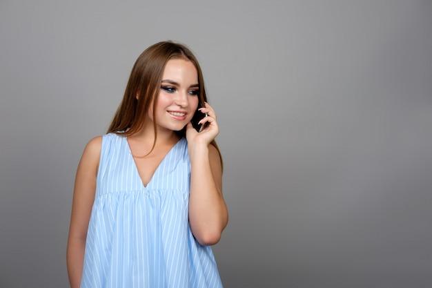 Junges mädchen, das mit dem telefon spricht und, lokalisiert auf grau lächelt