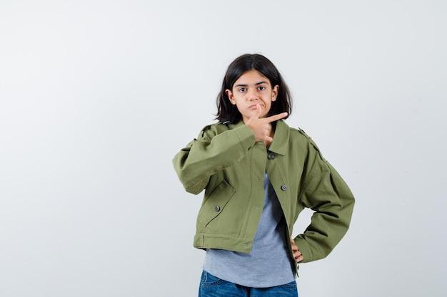 Junges mädchen, das mit dem zeigefinger nach rechts zeigt, während es die hand in grauem pullover, khakijacke, jeanshose an der taille hält und ernst aussieht. vorderansicht.