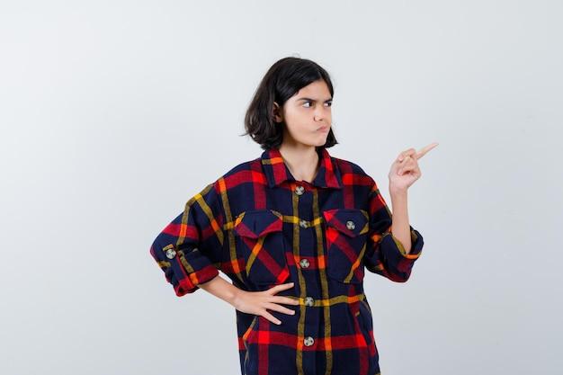 Junges mädchen, das mit dem zeigefinger nach rechts zeigt, während es die hand in kariertem hemd an der taille hält und ernst aussieht, vorderansicht.