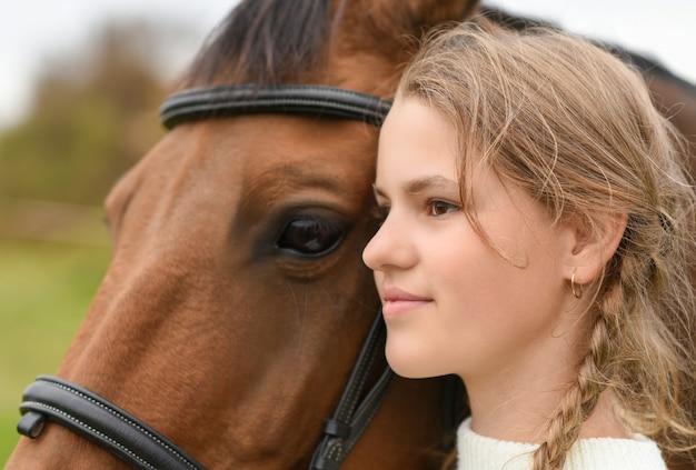 Junges mädchen, das mit einem pferd in der natur geht.