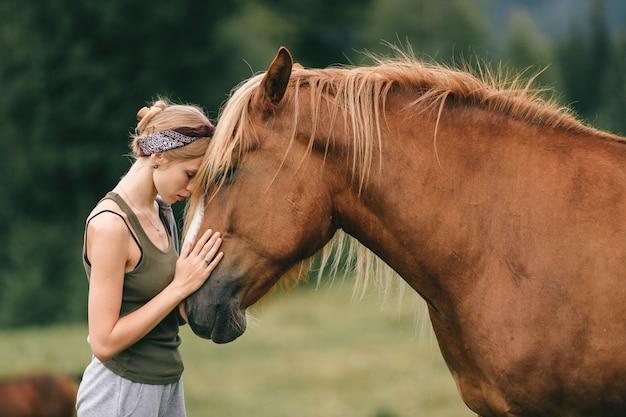 Junges mädchen, das mit einem pferd vertraulich steht.