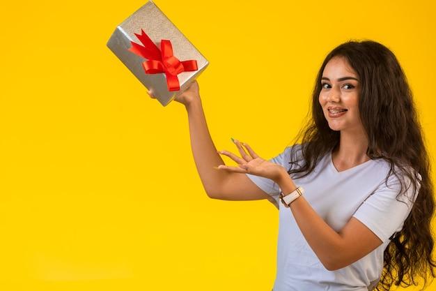 Junges mädchen, das mit einer geschenkbox in der hand aufwirft und lächelt.